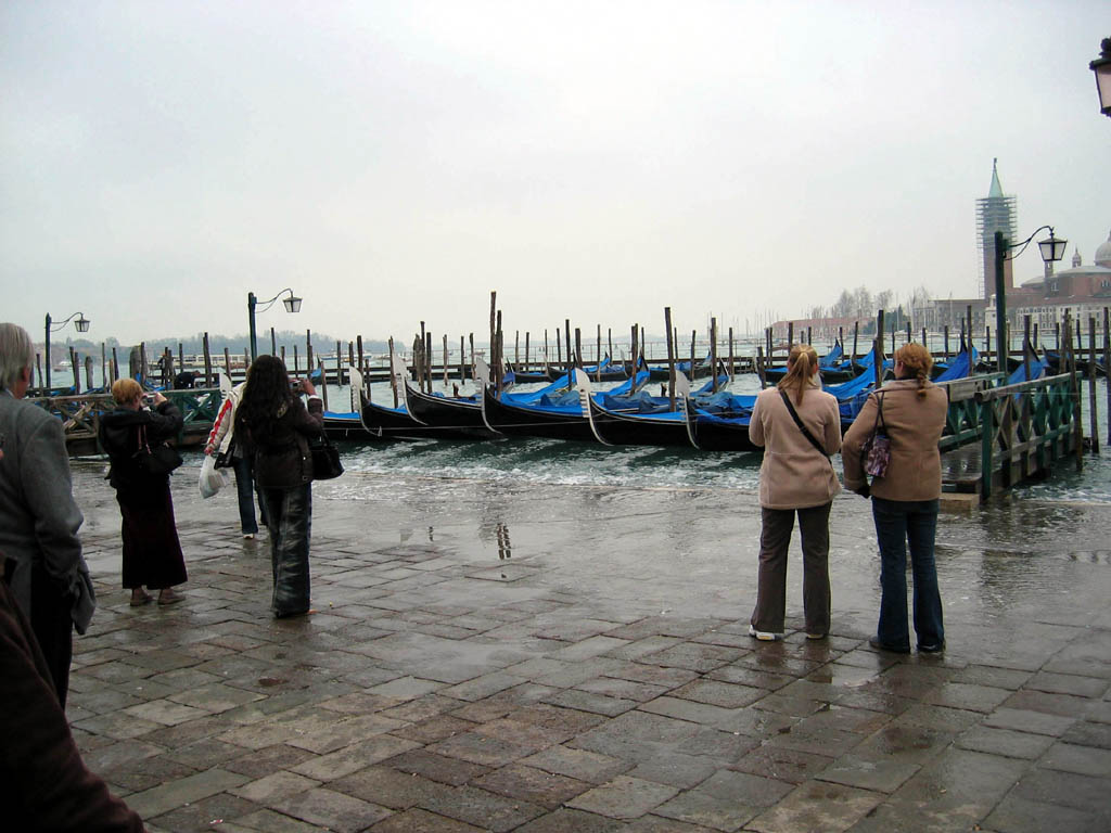 Gondolas docked near Piazza San Marco, with waterline lapping at sidewalk!